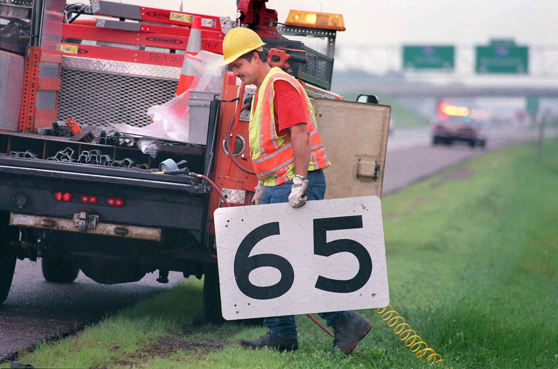 Myron Hennen of the Minnesota Department of Transportation's Oakdale sign shop carries away the old 65 mph speed limit sign after replacing it with a new 70 mph sign on southbound Interstate 35 south of Forest Lake, Minn. on June 24, 1997.