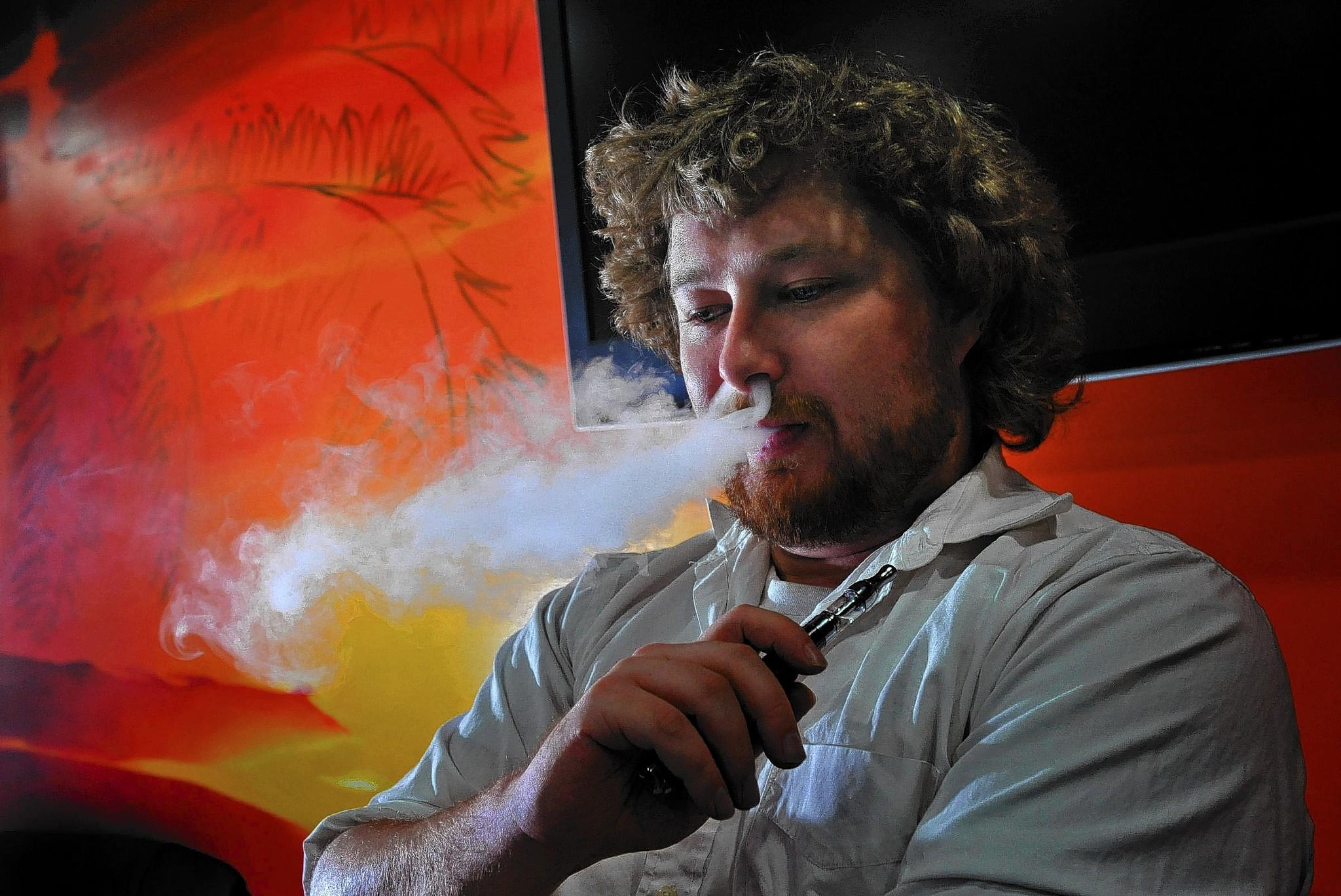Manager Sam Rogers smoke an electronic cigarette at the Kahuna Vapor shop in the Normandy Shopping Center in Ellicott City.