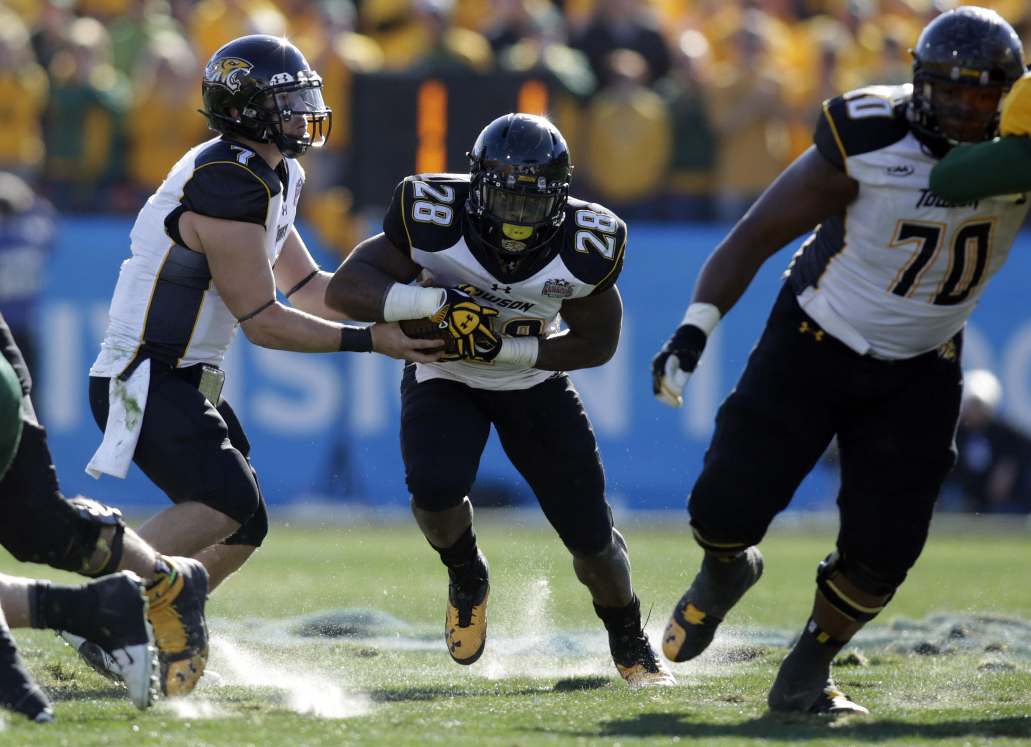 Towson's Peter Athens hands the ball off to Terrance West in the second quarter at Toyota Stadium, whose field condition drew criticism.