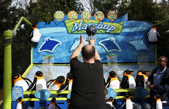 A Sea World guests play the Manta Matchup carnival style game by shooting a basketball through a hoop inside of the park on December 31, 2013.