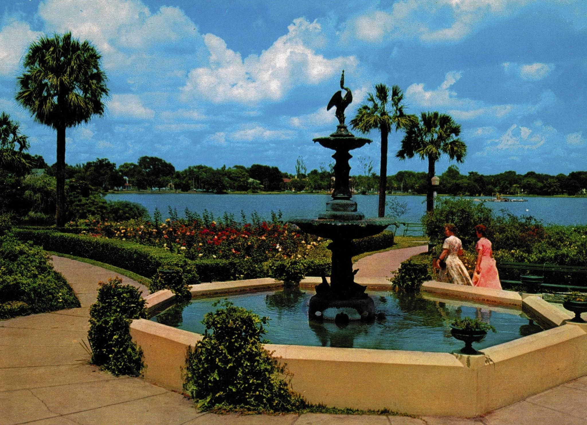 Two women walk past the 1914 Sperry Fountain at Orlando's Lake Eola Park in a scene on a 1950s postcard, before the construction of the landmark green-domed fountain in the middle of the lake.