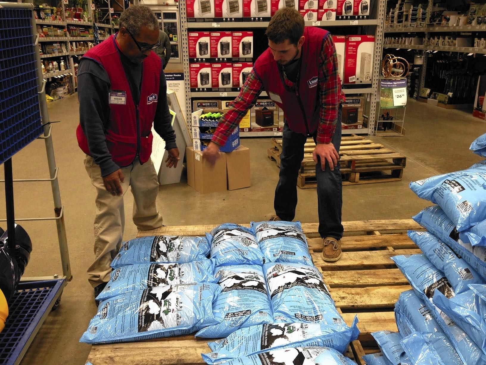 From left, Lowe's employees Marvin Borden and Jonathan Banner stock salt pellets to prepare for an arctic blast that's expected to hit the region Monday afternoon.