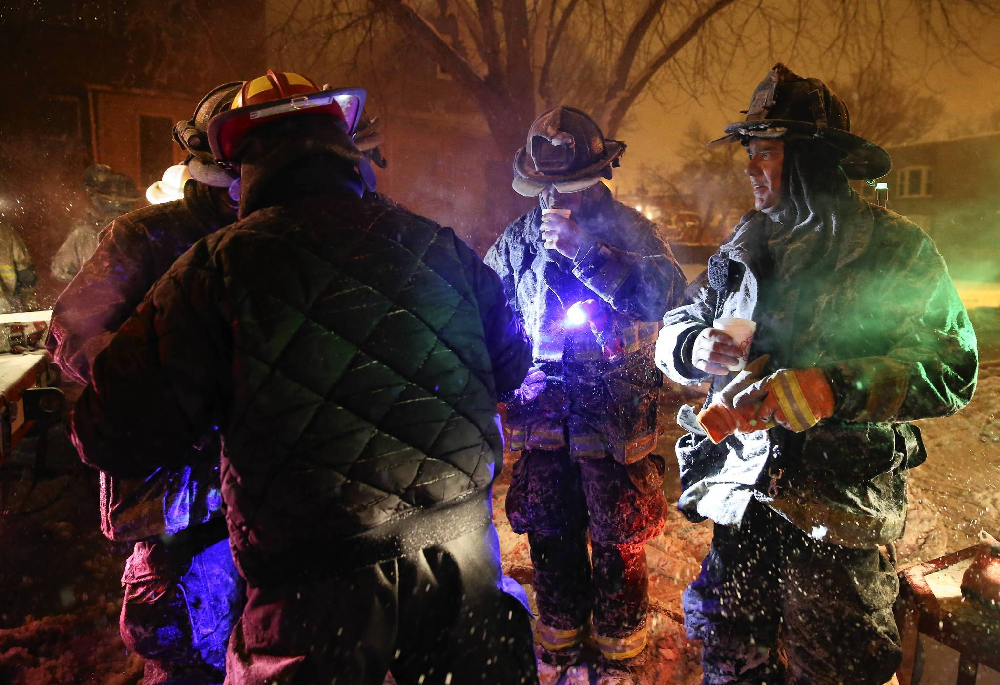 Chicago firefighters from Engine 123 keep warm with hot chocolate at the scene of a 211 alarm fire in the 5400 block of South Justine Avenue in Chicago Sunday night.