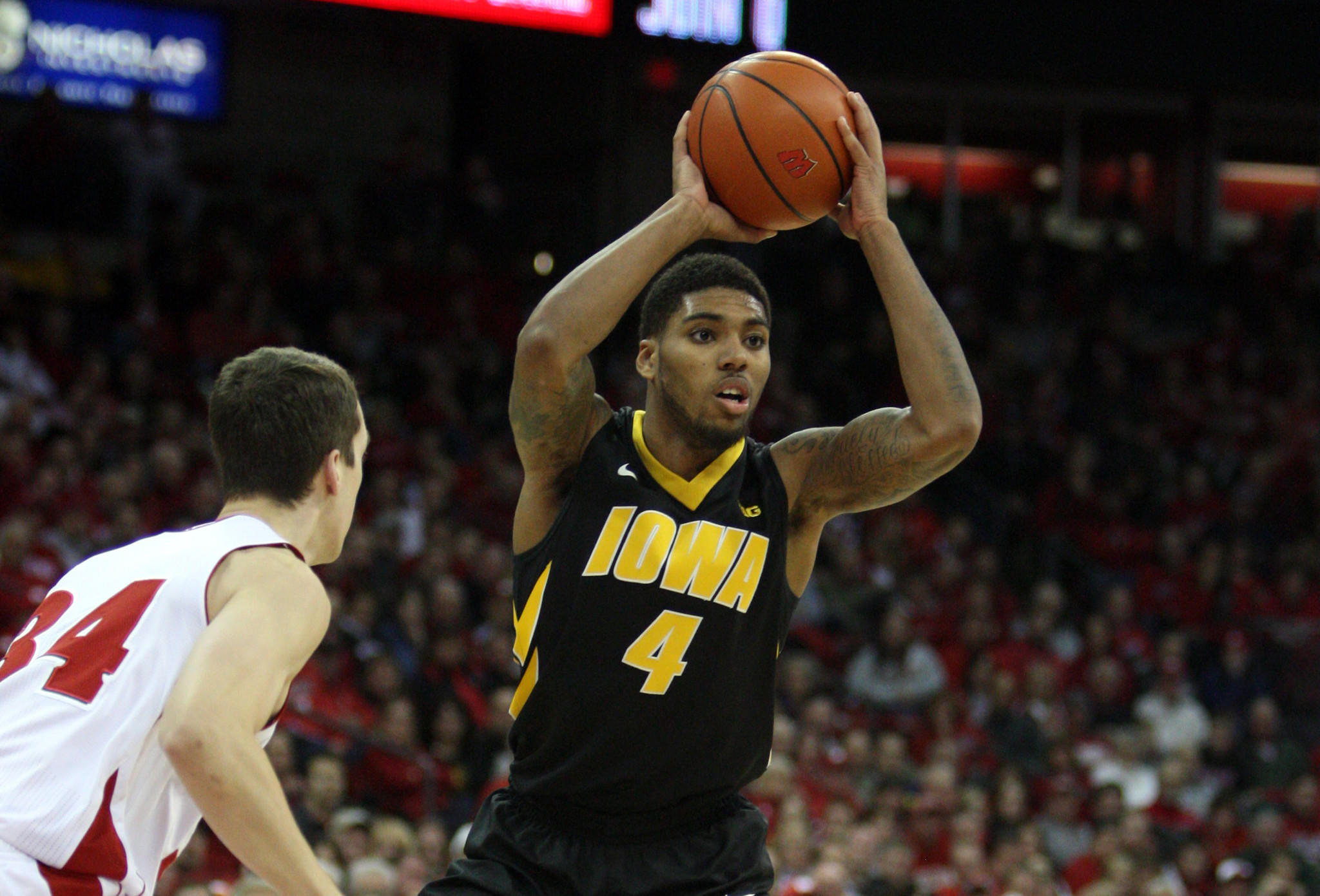 Iowa's Roy Marble looks to pass as Wisconsin's Zach Bohannon defends at the Kohl Center.
