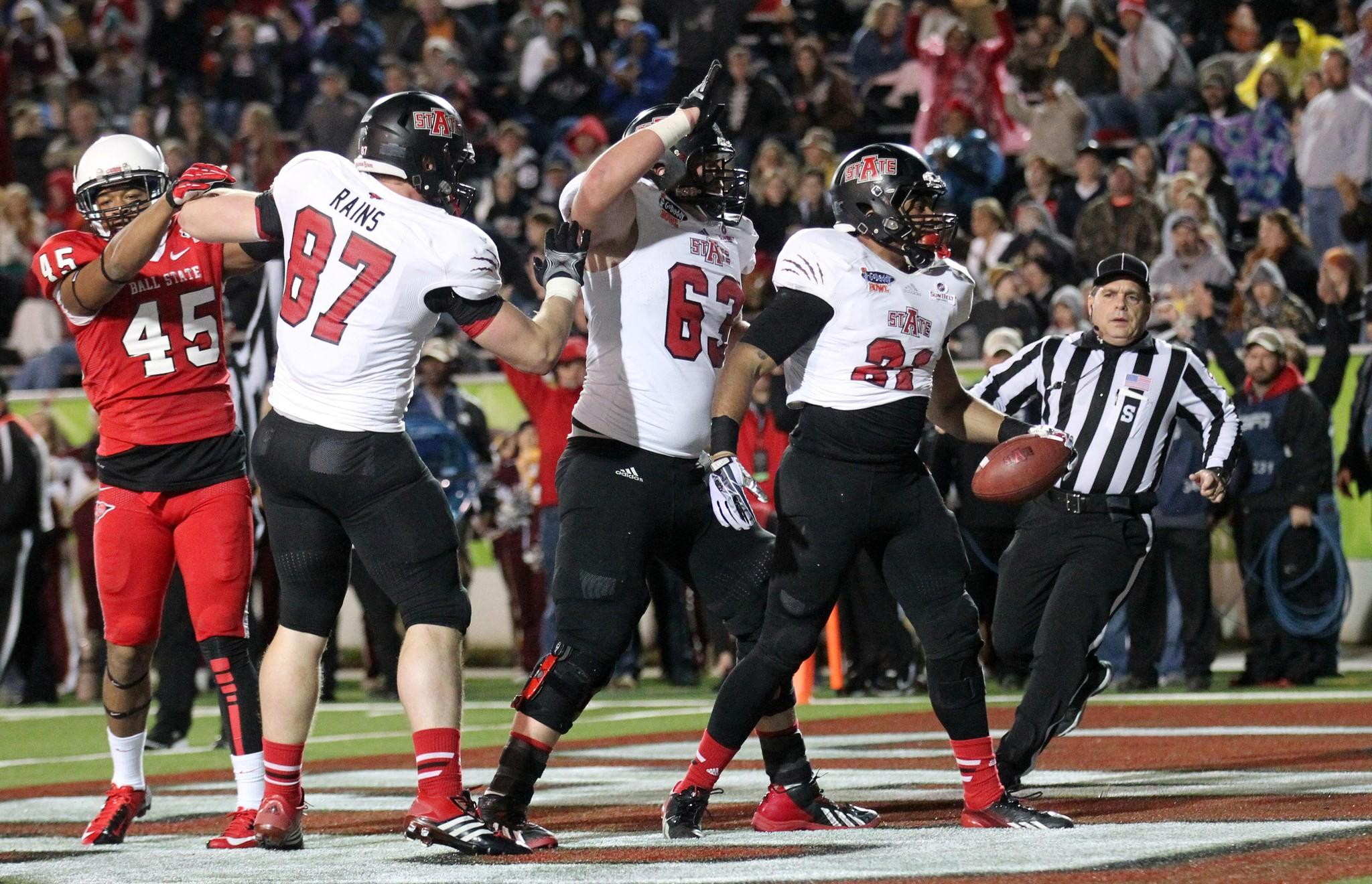 Arkansas State running back Sirgregory Thornton is congratulated by offensive linesman Cliff Mitchell and teammates after scoring a touchdown in the first half.