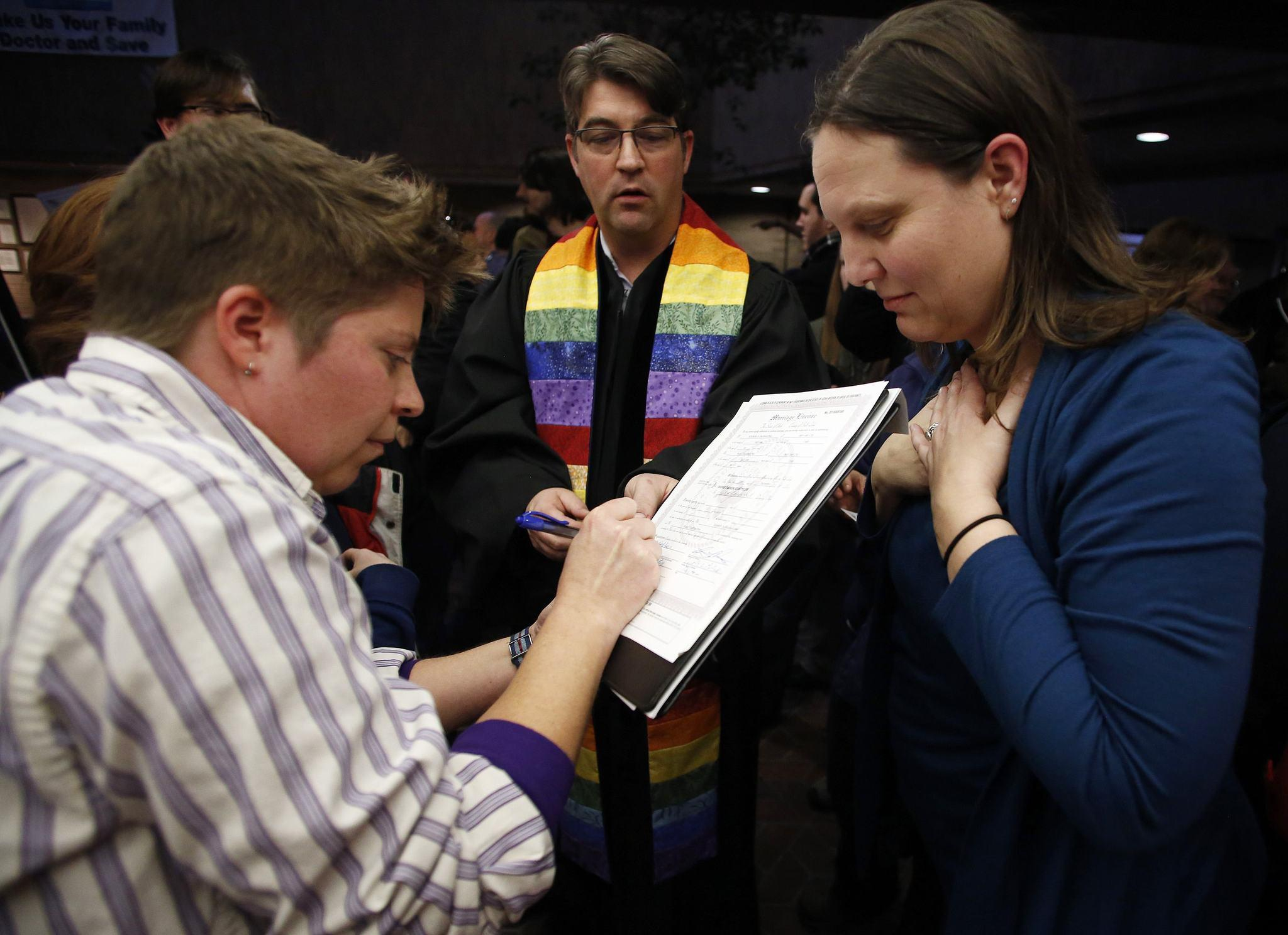 Ruth Hackford-Peer, left, and Kim Hackford-Peer sign their marriage certificate after getting married as Reverend Curtis Price watches at the Salt Lake County office building in Salt Lake City, Utah, December 20, 2013.