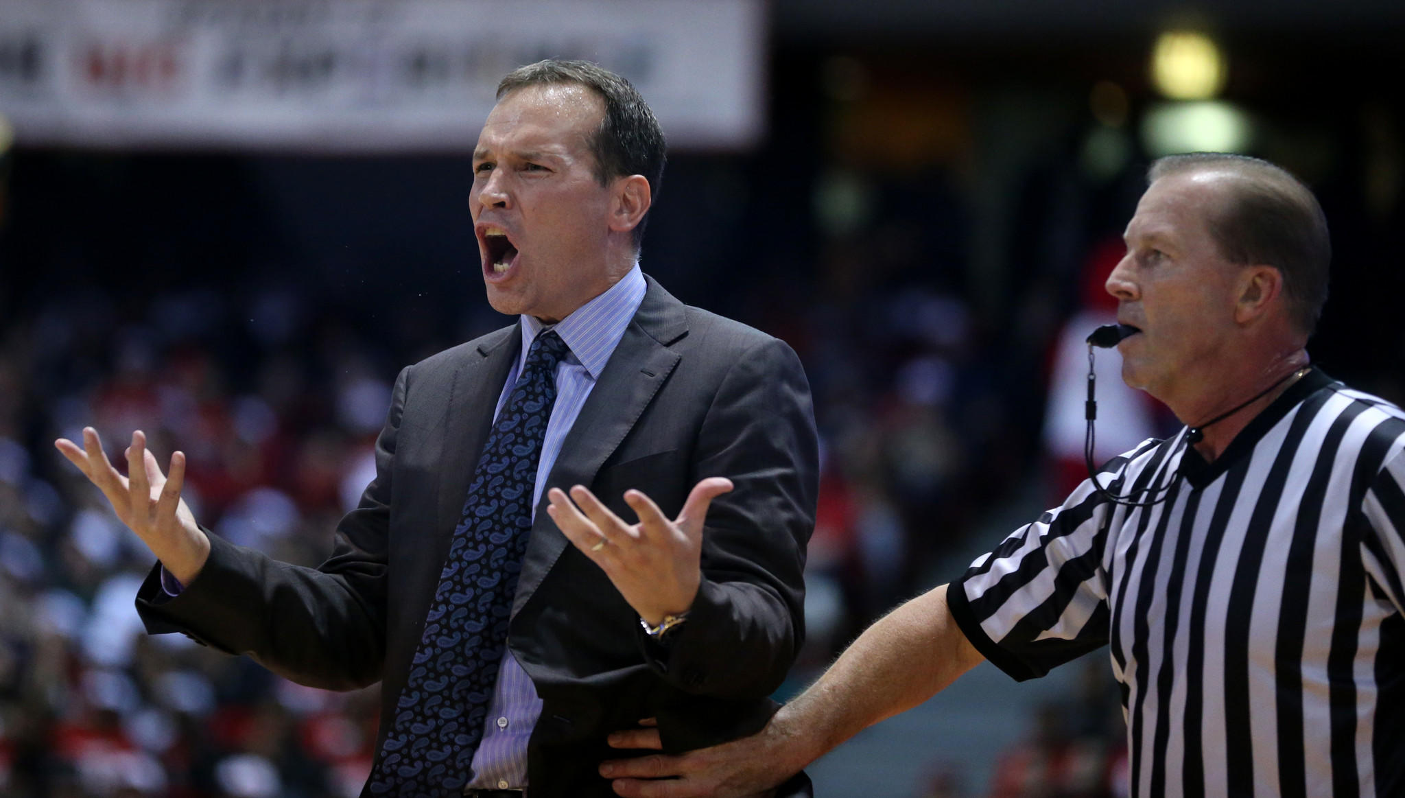 A referee holds back Northwestern basketball coach Chris Collins as he yells at his team in the first half against UIC.