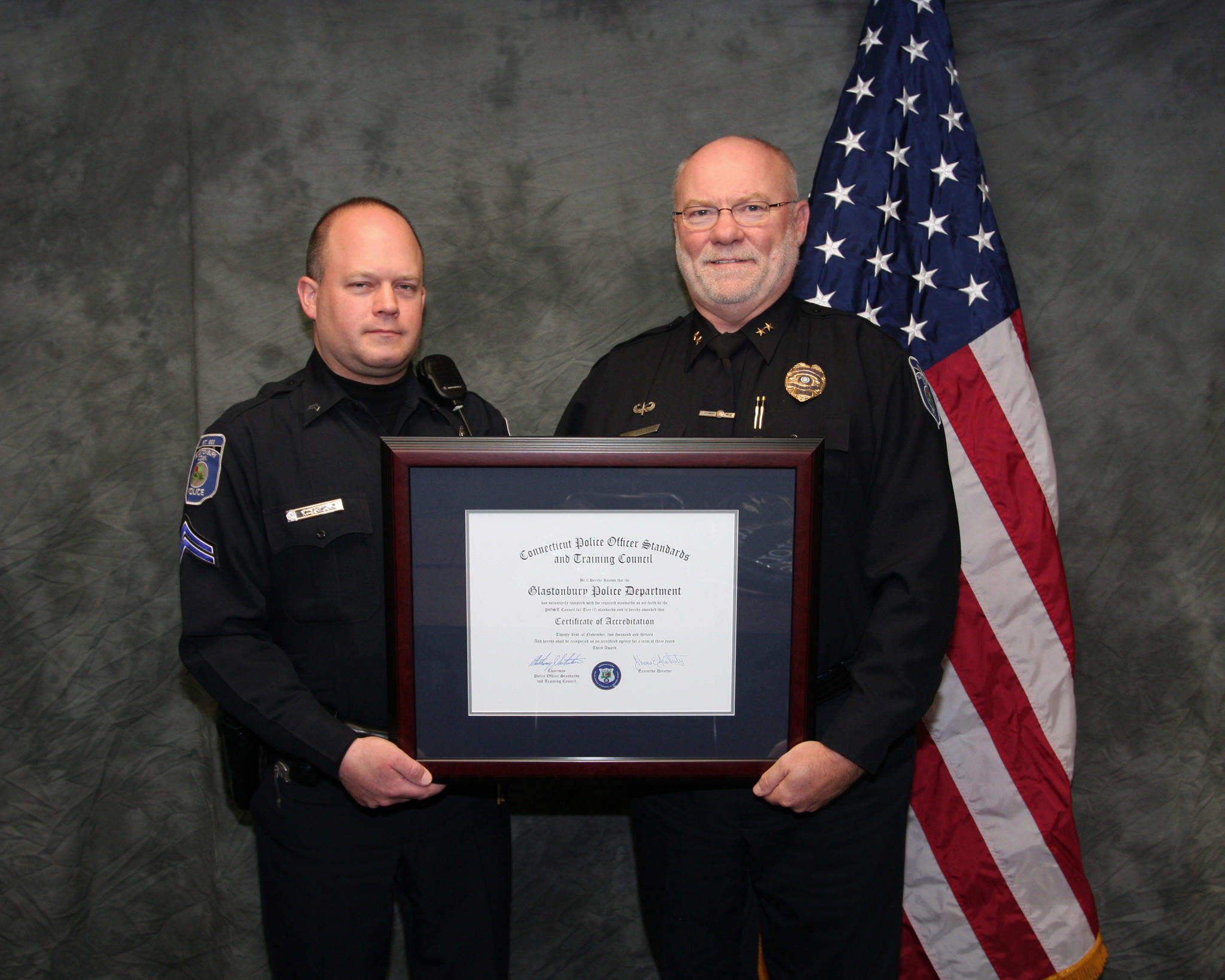 Agent Kevin Szydlo (left) and Police Chief David A. Caron hold the re-accreditation plaque.