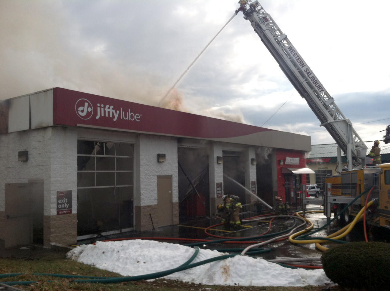 Smoke pours from the roof of the Jiffy Lube on Lehigh Street in Salisbury Township on Monday afternoon as firefighters battle the four-alarm blaze.