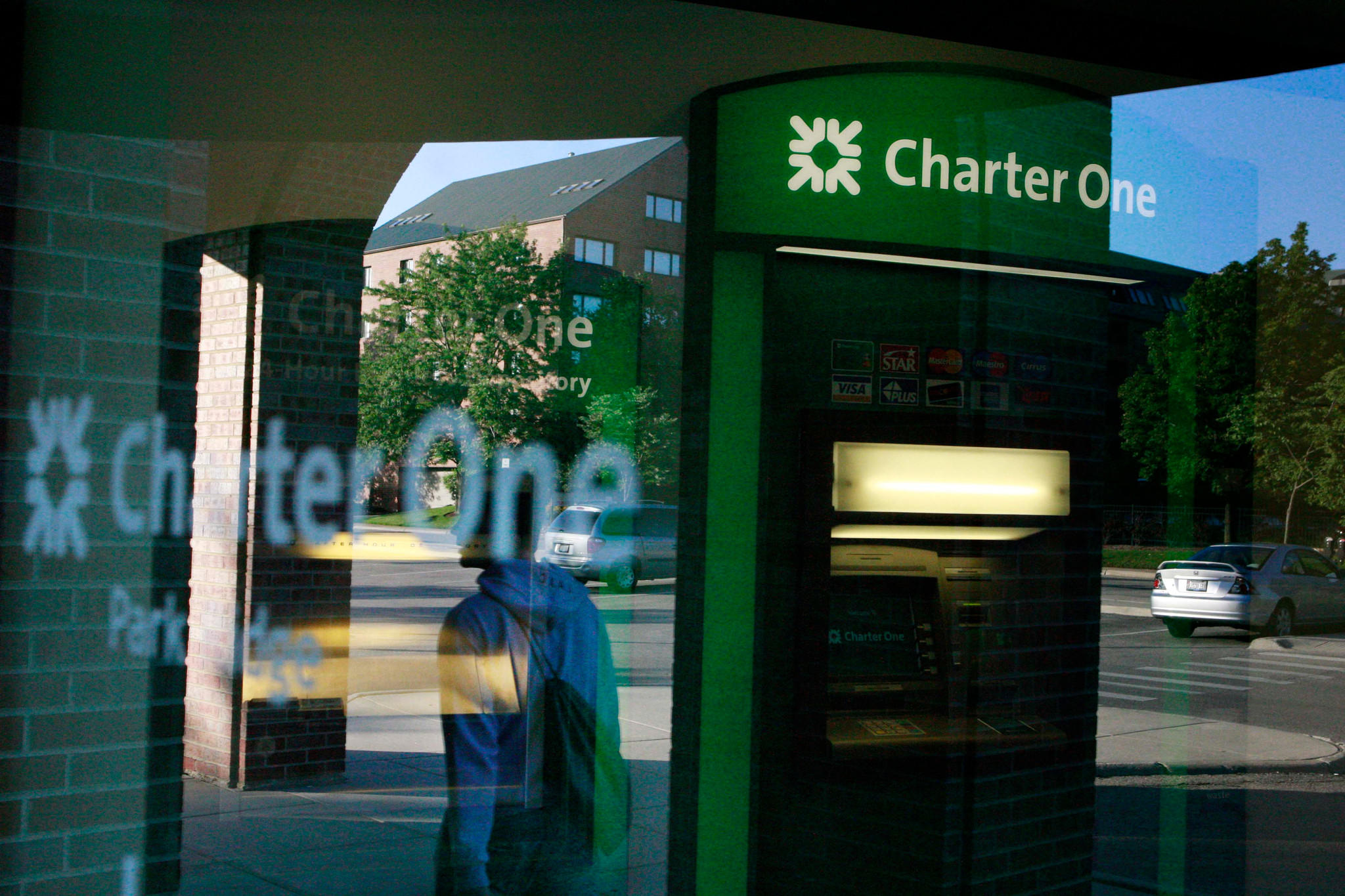 A woman is reflected in the window of the Charter One Bank in Park Ridge.