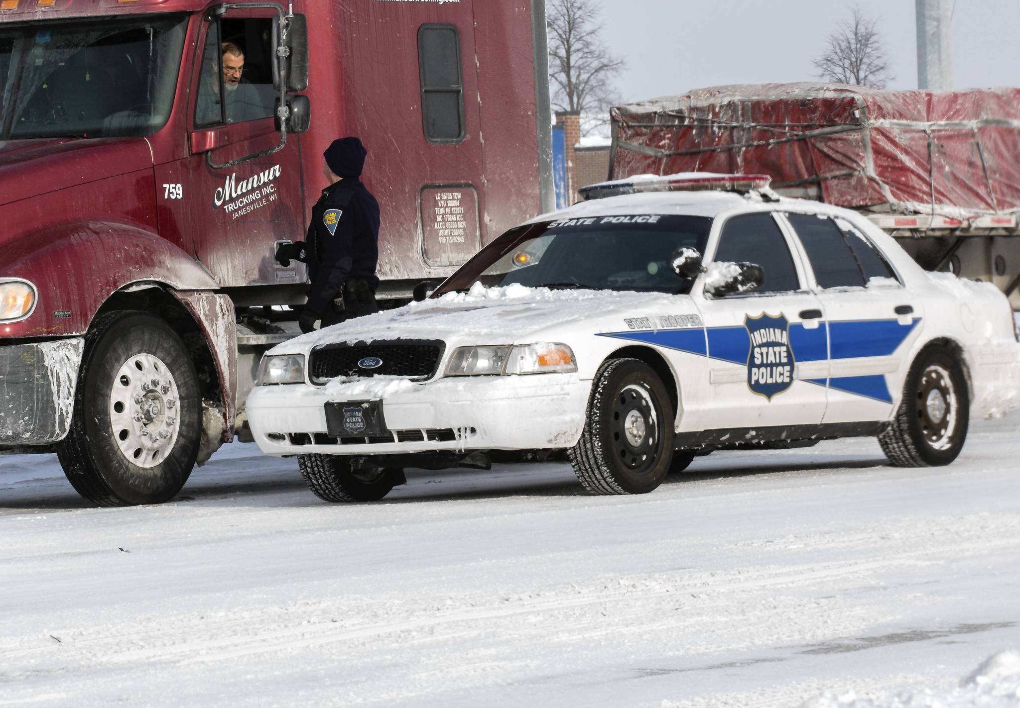 An Indiana state trooper advises a truck driver to move on after the opening of I-65 at U.S. 30 in Merrillville, Ind., on Monday.