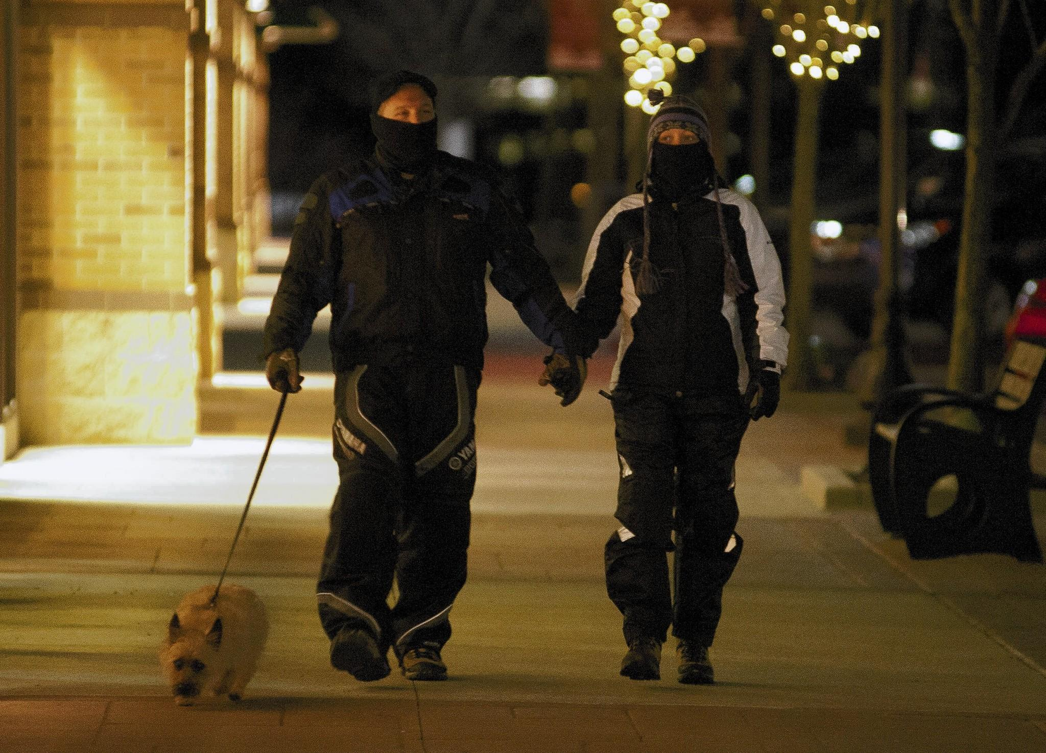 Mark and Jennifer Hogen of Coopersburg walk their dog Buddy in the frigid temperatures Monday night at the Promenade Shops at Saucon Valley.
