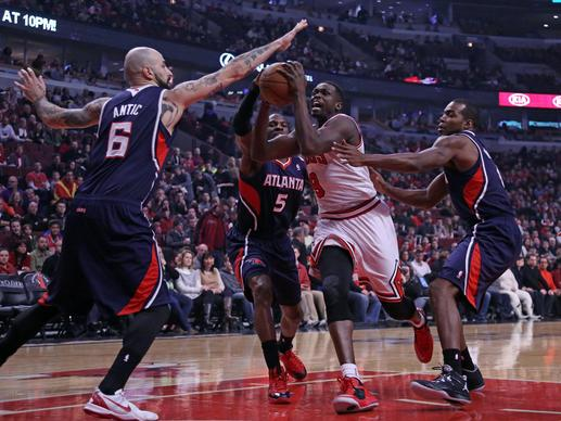 The Hawks' Pero Antic blocks the shot of Luol Deng during the first quarter.