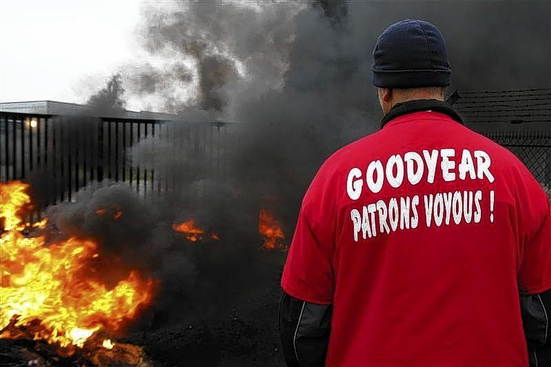 An employee of U.S. tire-maker Goodyear stands in front of burning tires at the entrance of the plant in Amiens, northern France, to protest job cuts and the project to close the French plant in Amiens in this Nov. 18, 2013 file picture.