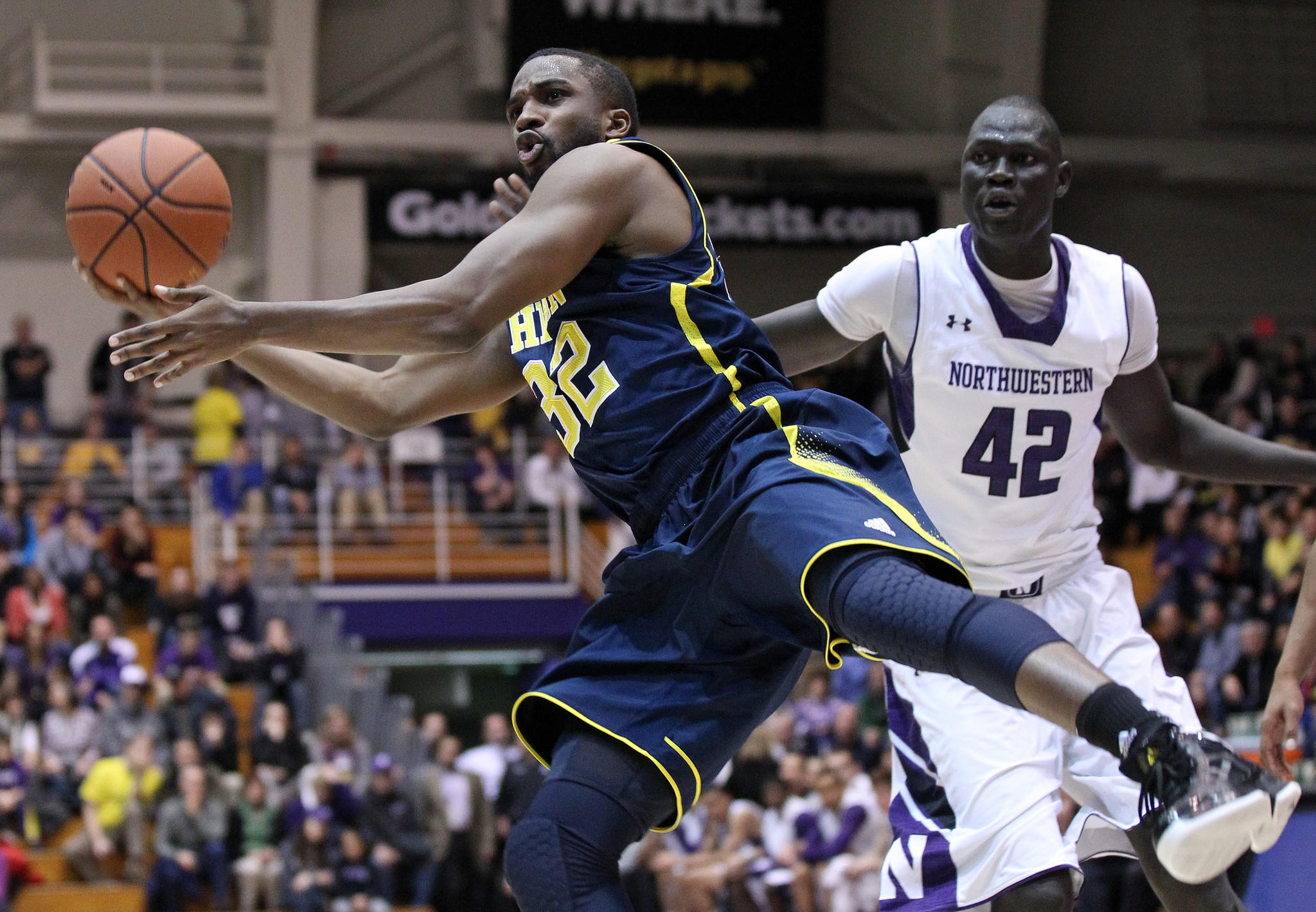 Michigan's Corey Person (32) is fouled by Northwestern's Chier Ajou (42) in the second period at Welsh-Ryan Arena.