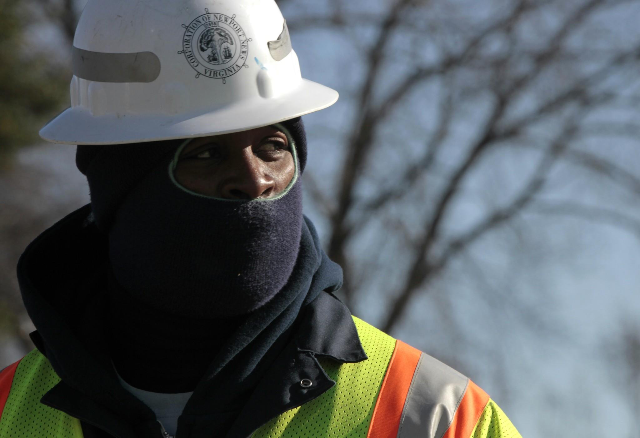 Ronald Boone covers his face against the cold while repairing a water main leak with Newport News Waterworks near the intersection of Nettles Drive and Winterhaven Drive on Tuesday morning.