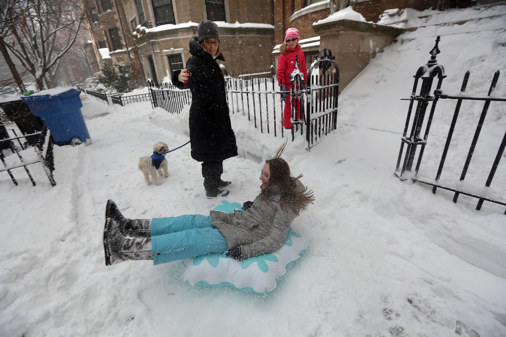Jen O'Brien and her daughter Sydney, back, watch as her other daughter Samantha, 12, sleds down the front steps.