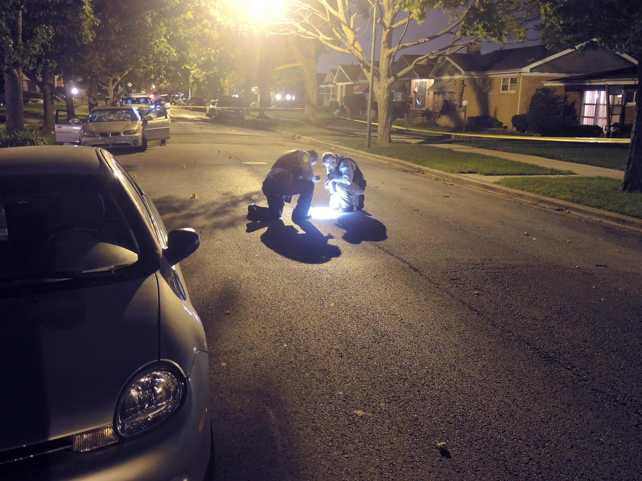 Police investigate the scene of a homicide in July. Adam Sege/Chicago Tribune