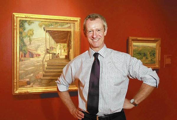 "Malcolm Warner recently completed two years as executive director of the Laguna Art Museum, where he stands with ""The Old Post Office"" by Joseph Kleitsch, one of the museum's signature pieces."