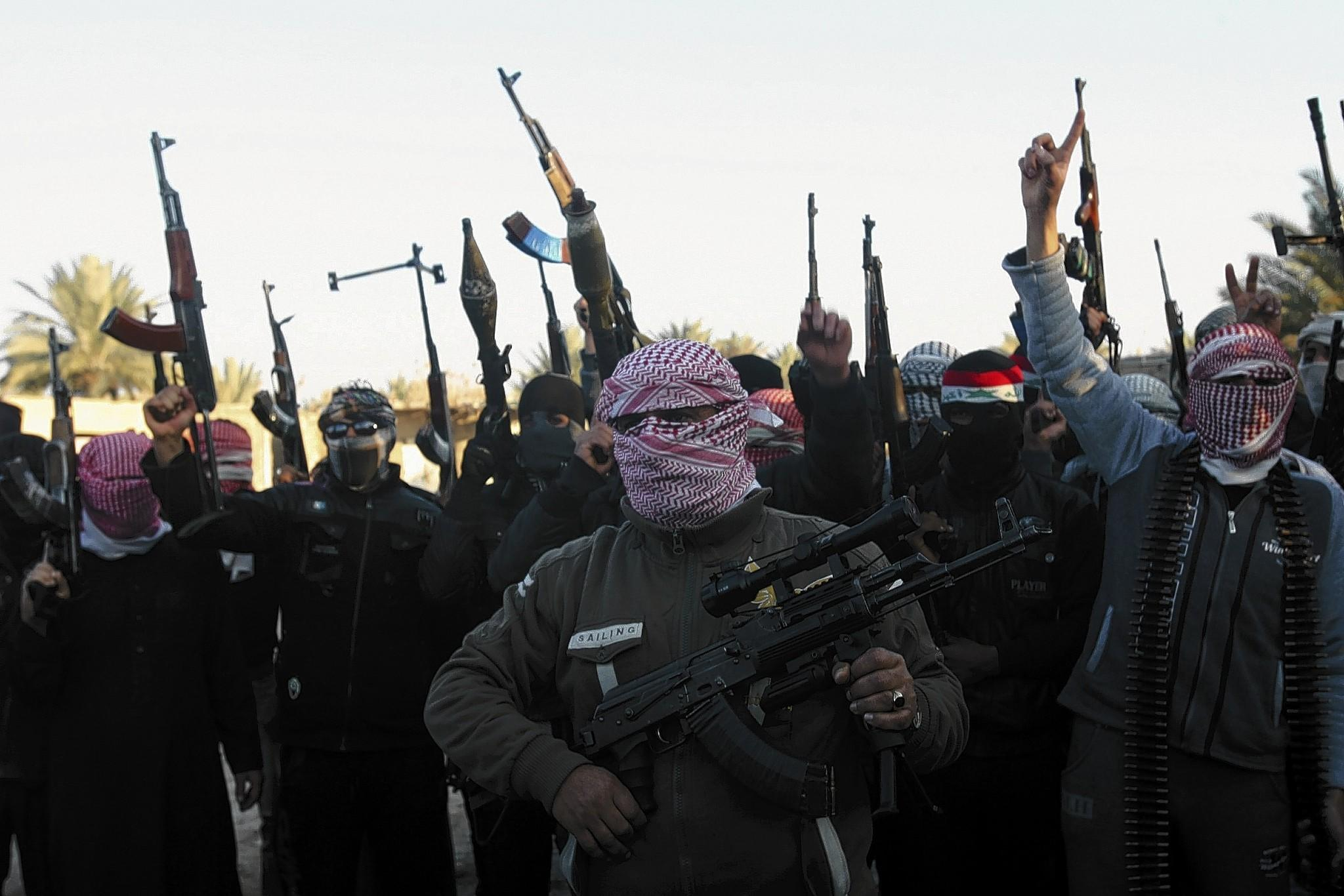 Masked gunmen chant slogans during a protest Tuesday in Fallujah against Iraq's Shiite-led government.