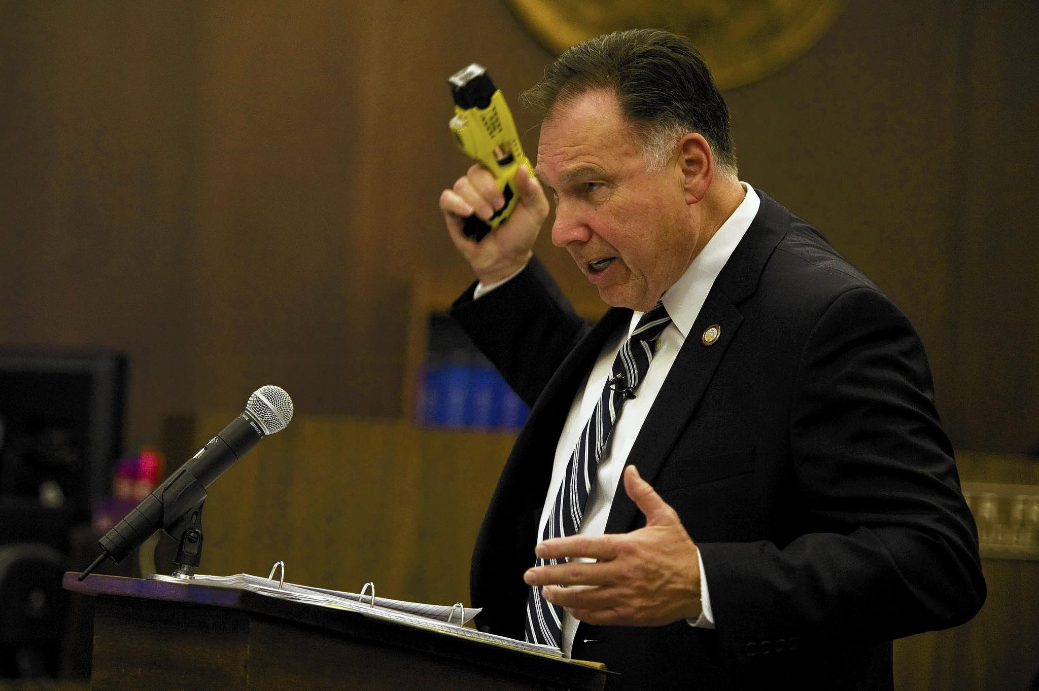 During closing arguments in the trial of two former Fullerton police officers in the death of a mentally ill homeless man, Orange County Dist. Atty. Tony Rackauckas holds a Taser similar to the one used by one of the officers as a blunt-force weapon.