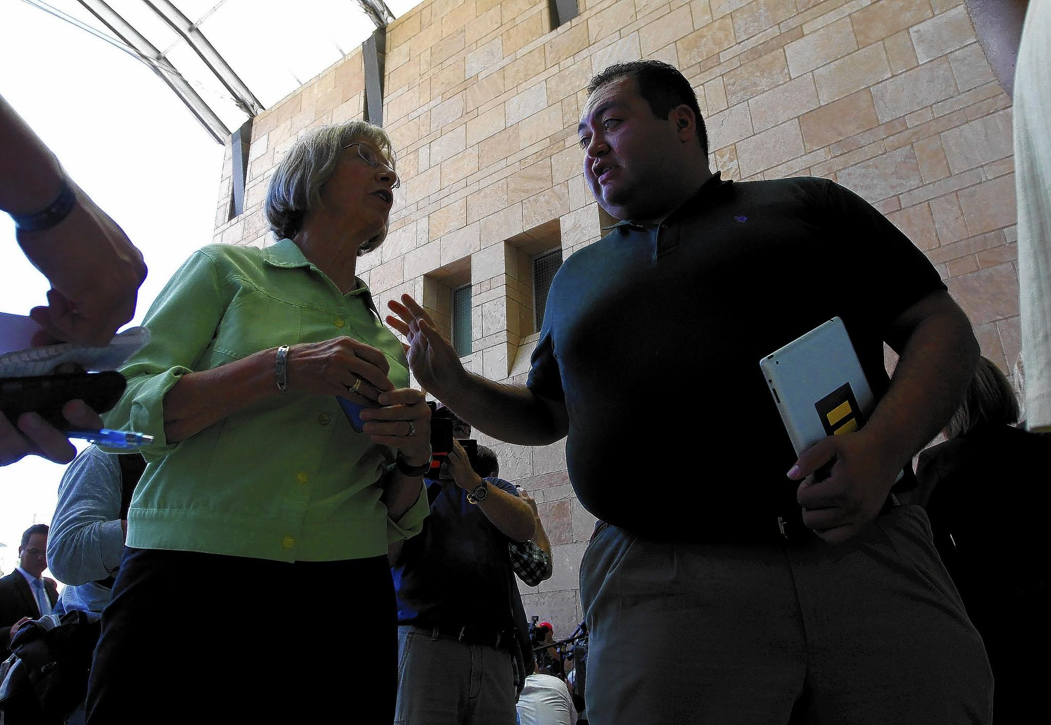 Daniel Hernandez Jr. speaks with Pam Simon, a former member of Rep. Gabrielle Giffords' staff, in Tucson in 2012. Simon was one of the wounded in the 2011 shooting.