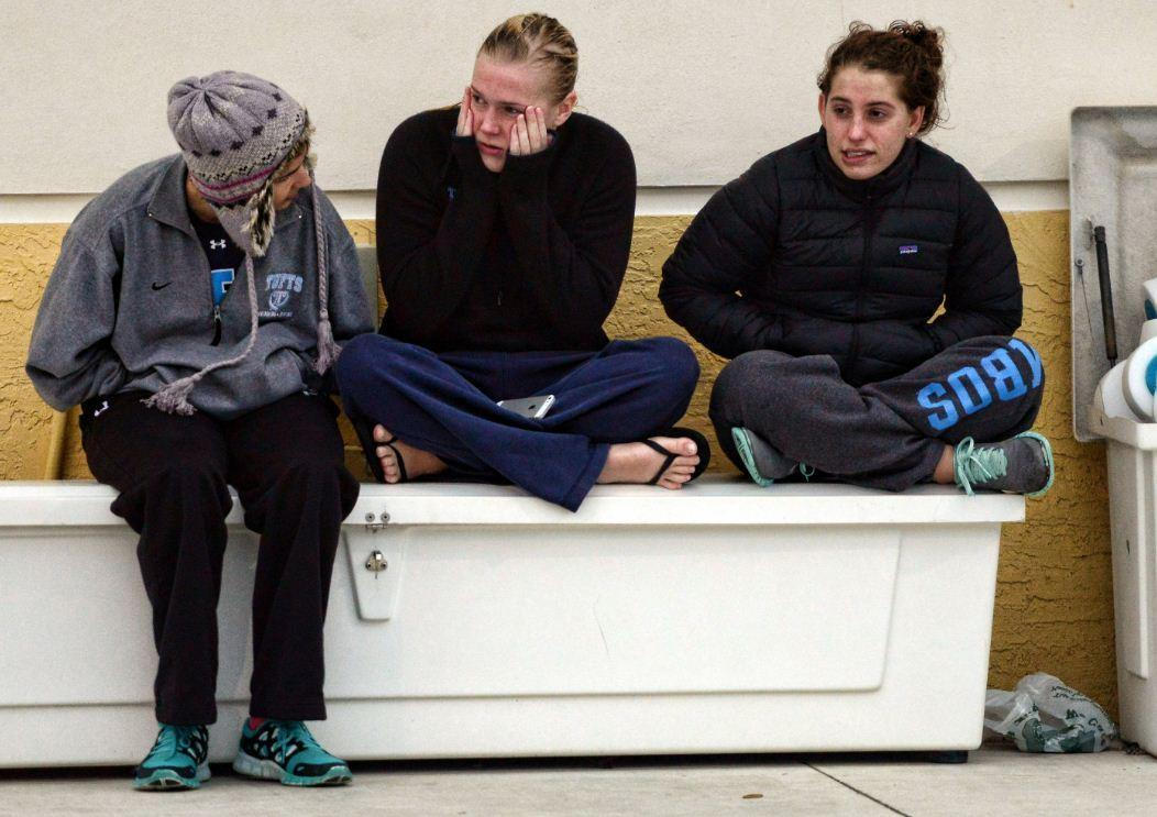 Swimmers from the Tufts University swim team of Medford Mass., Simonne Dubois, left, Emma Vanlieshout, center, and Maddie Golison, right, try to keep warm after getting out of the pool after team practice at the Pompano Beach Aquatic Center, Tuesday, Jan. 7, 2014.