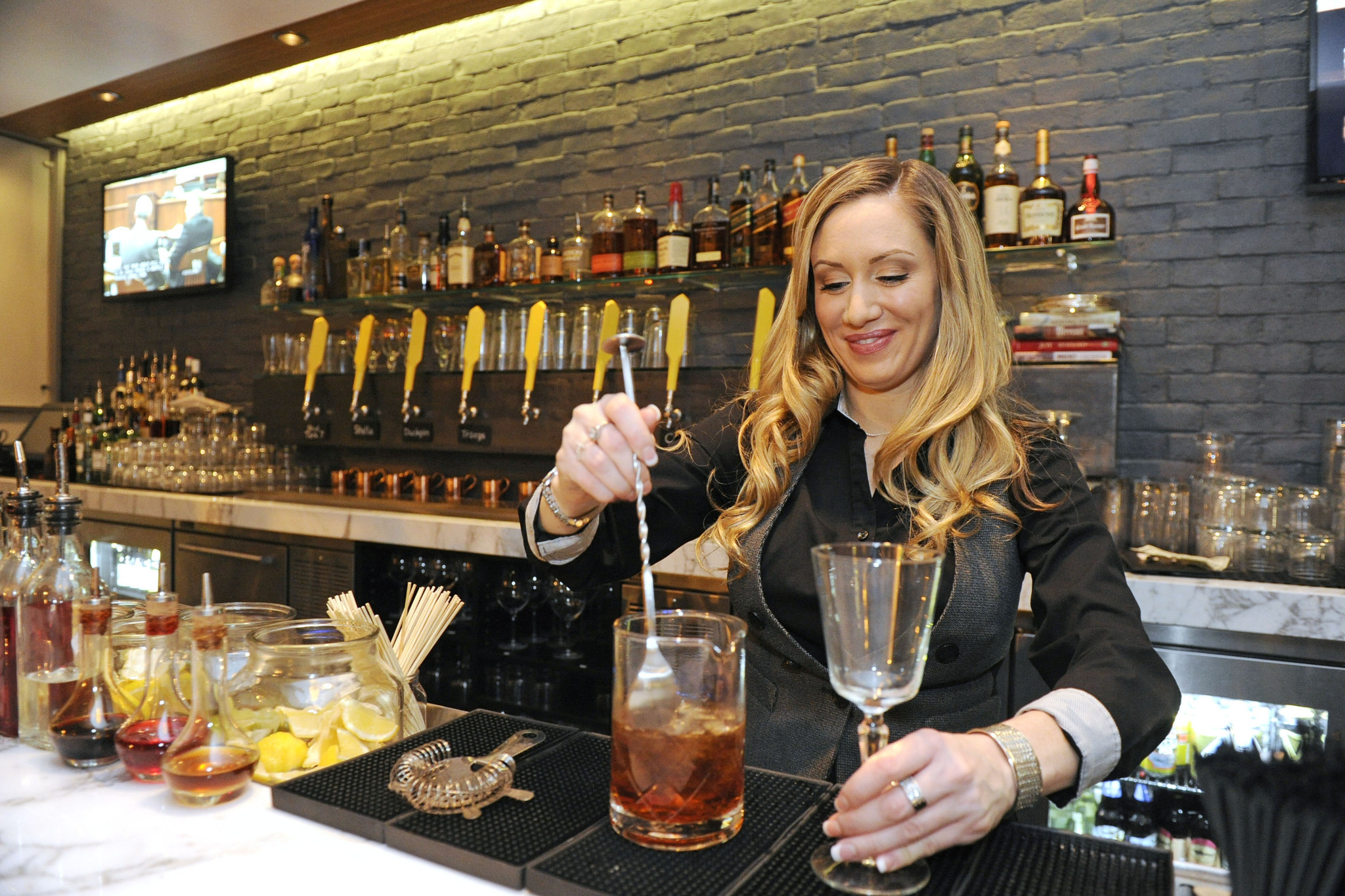 Ray Zanin, bar manager of City Bar at City Cafe, mixes a drink on a recent Friday night.