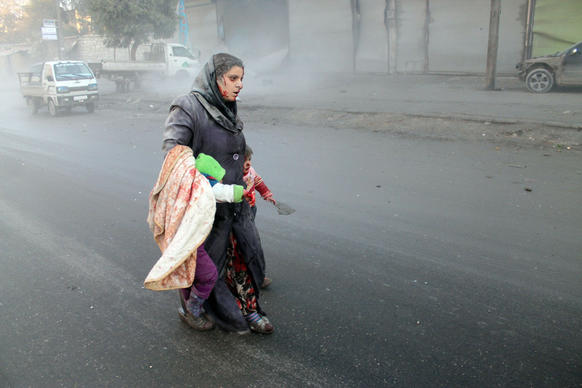 A wounded Syrian woman walks with her children following airstrikes on a rebel area of the war-torn northern city of Aleppo.
