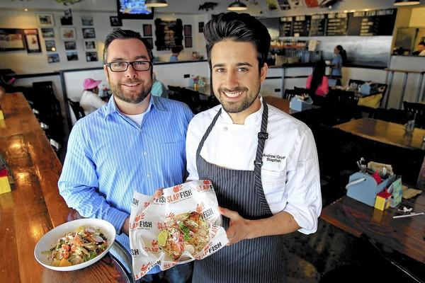 Co-founders Andrew Gruel, 33, center, and Jethro Naude at Slapfish in Huntington Beach on Tuesday. Slapfish started out as a gourmet food truck service in late 2009 but has evolved into a restaurant business since April of 2012.