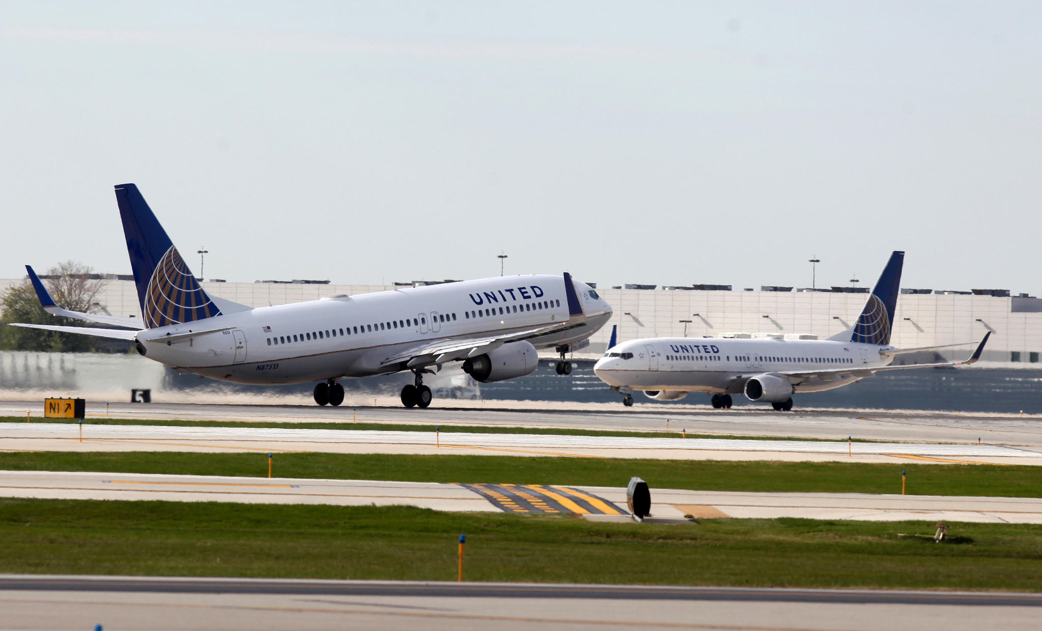 A United Airlines plane takes off as another lands at Chicago O'Hare International Airport in Chicago, Friday, Oct. 25, 2013.