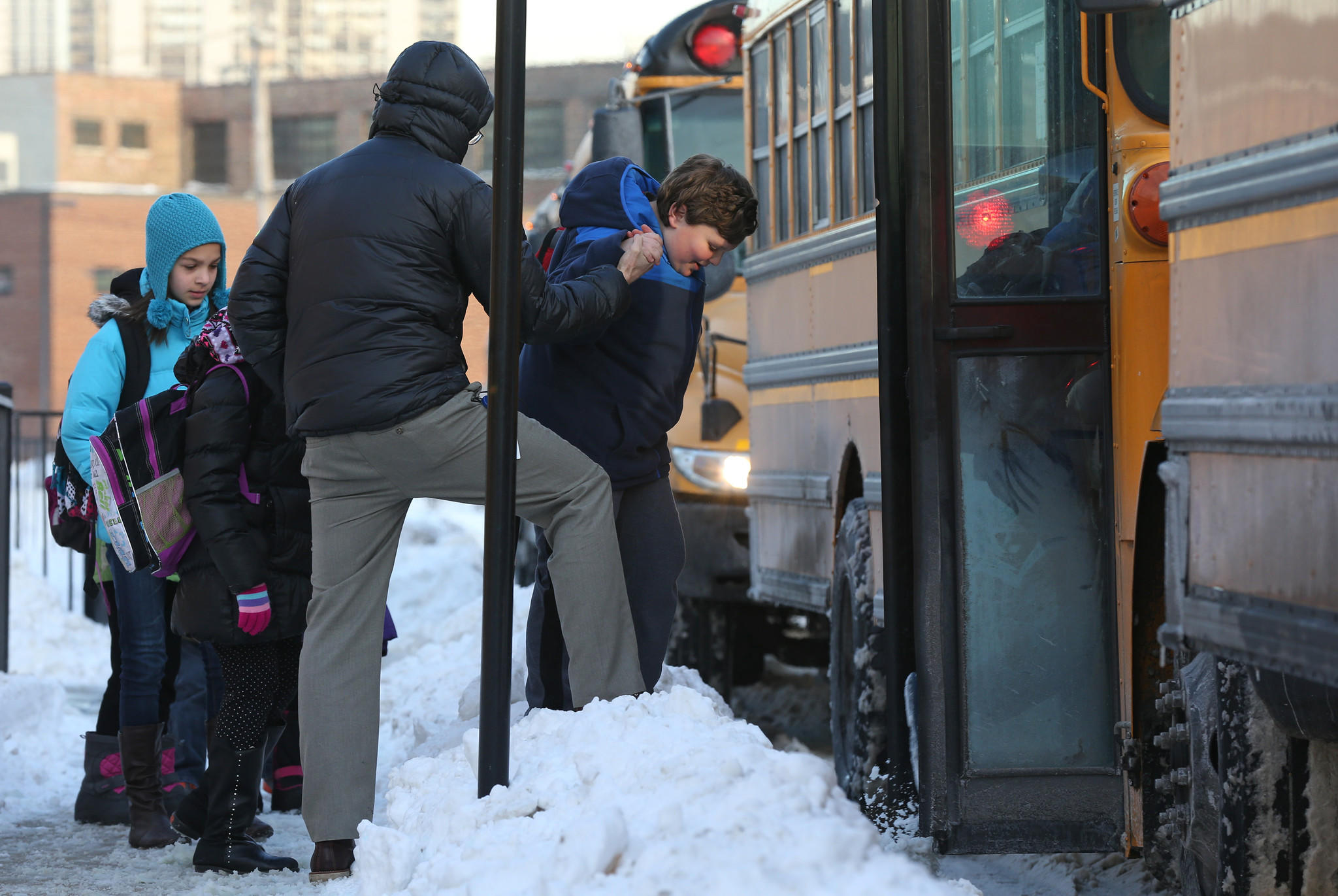 Spanish teacher Zach Schroeder helps students navigate the snow and onto buses after class at Skinner North Classical School, 640 W. Scott St. on Wednesday.