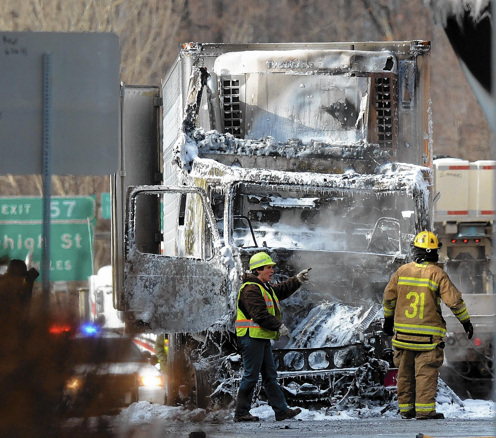 Firefighters inspect the two tractor-trailers that crashed Wednesday morning on Interstate 78 in Salisbury Township. One truck cab, above, broke into flames when it rear-ended the other big rig. A passer-by helped pull the trucker and his passenger out. Police said no one had life-threatening injuries.