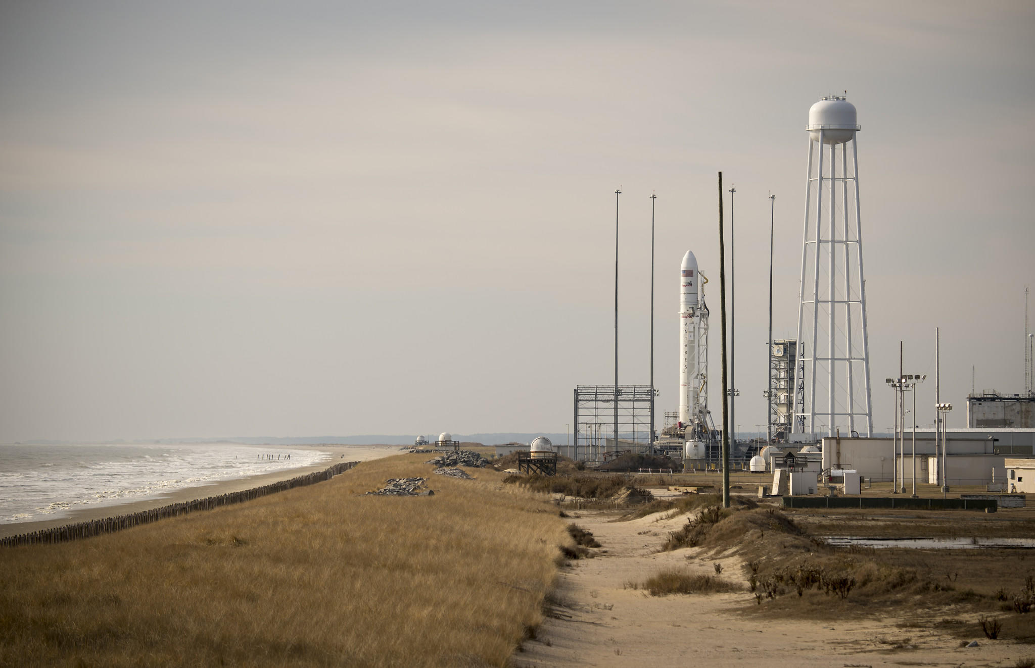 The Orbital Science Corporation Antares rocket is seen shortly after it was raised into position at launch Pad-0A, Tuesday, December 16, 2013, at NASA's Wallops Flight Facility, Wallops Island, VA. The Antares will launch a Cygnus spacecraft on a cargo resupply mission to the International Space Station. The Orbital-1 mission is Orbital Sciences' first contracted cargo delivery flight to the space station for NASA. Among the cargo aboard Cygnus set to launch to the space station are science experiments, crew provisions, spare parts and other hardware. Launch is scheduled for 9:19 p.m. EST on Thursday, Dec. 19. Weather permitting, it may be widely visible along the east coast of the United States. Photo Credit: (NASA/Bill Ingalls)