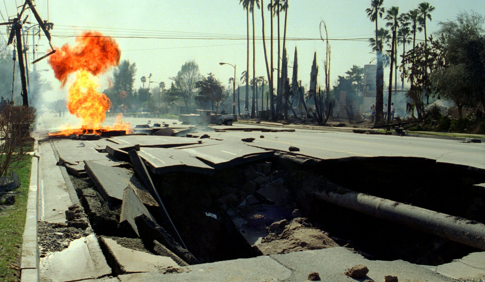 Flames billow from a ruptured gas main beyond a crater in Granada Hills after the 1994 Northridge earthquake.