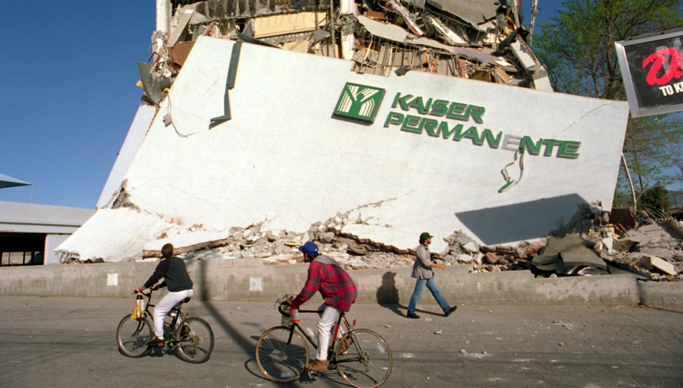 Cyclists roll past the remains of a collapsed Kaiser Permanente clinic and office building in Granada Hills following the Northridge earthquake.