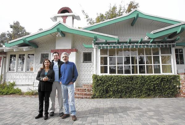 The Urth Caffe's Shallom and Jilla Berkman (center and left, respectively) stand with architect Todd Skenderian outside The Cottage restaurant property on Tuesday. The team will renovate the structure to its original specifications from the '20s.