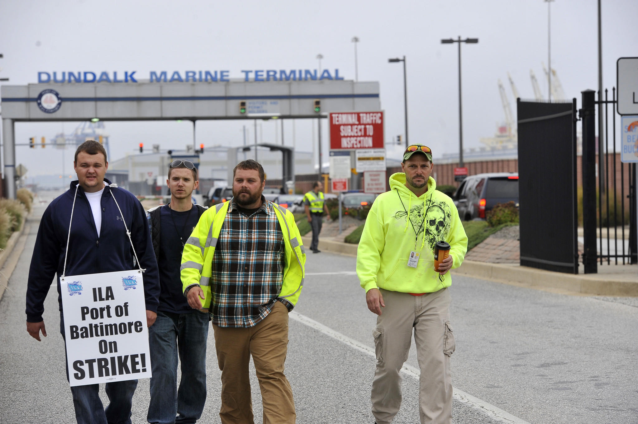 Striking longshoremen, left to right, John Watts, Sparrows Point, Victor McQuay, Jr, Sparrows Point, Ronald Wozniak, Sparrows Point, and Thomas Deters, Pasadena, walk back to the picket line after getting a look at a ship in port. They say they saw the vehicle carrier being unloaded.