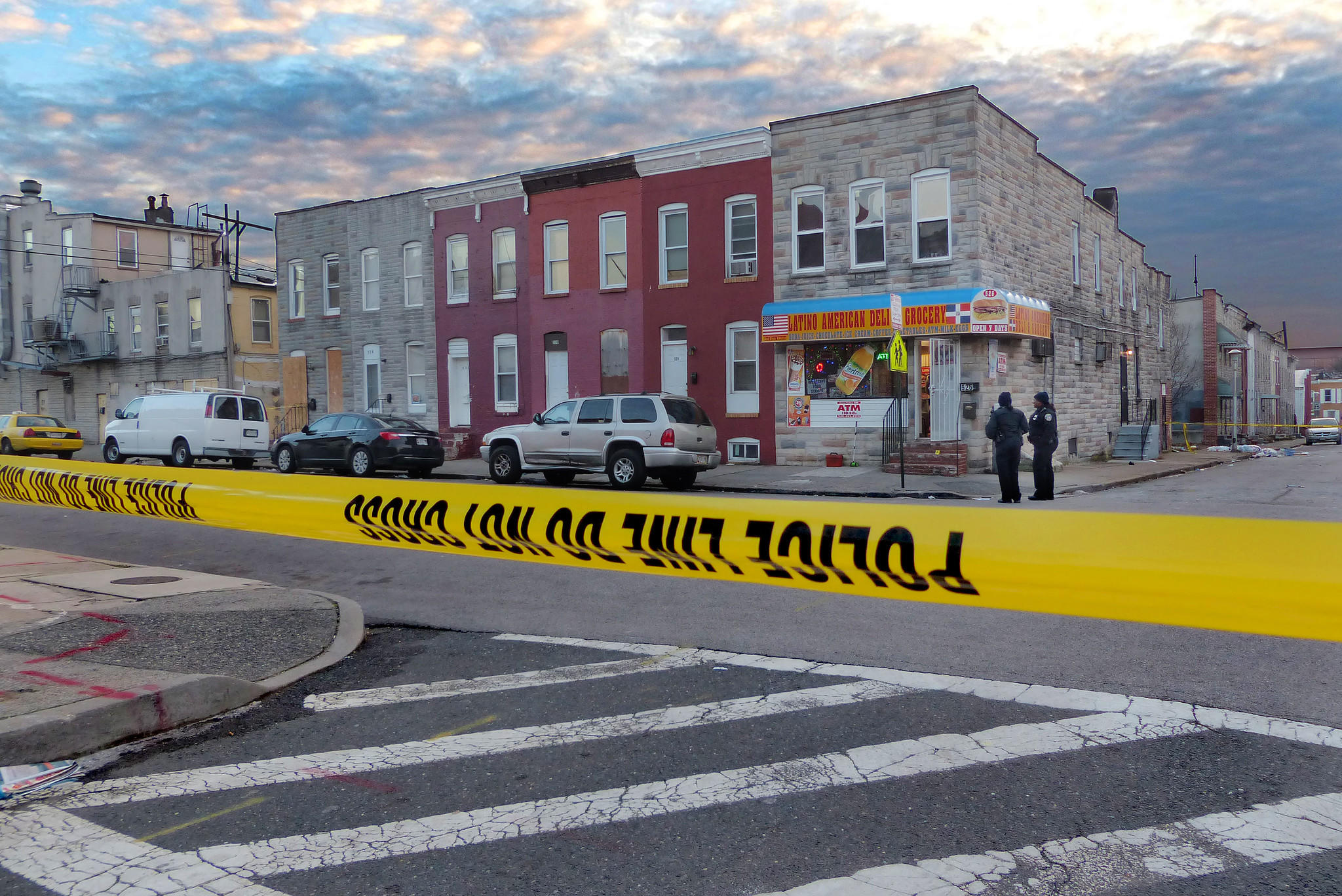 Crime scene tape stretches across Christian Street at the scene of bloodshed following a shooting at a Southwest Baltimore corner store.