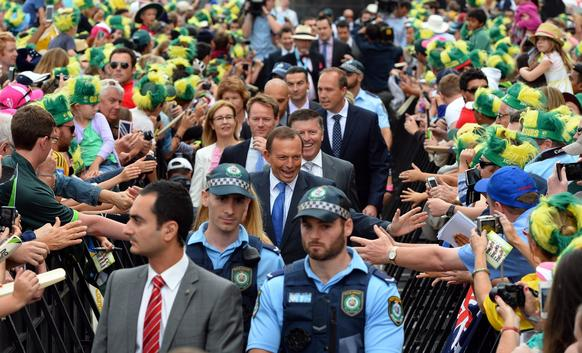 """Security officers escort Australian Prime Minister Tony Abbott through cricket fans that have gathered to celebrate Australia's victory over England in the Ashes Test series at the Sydney Opera House during a ceremony on January 7, 2014. Abbott has competed in an Ironman triathlon (causing hubbub when he billed travel expenses to taxpayers). Abbott """"regularly cycles up and down hills near Parliament House."""""""