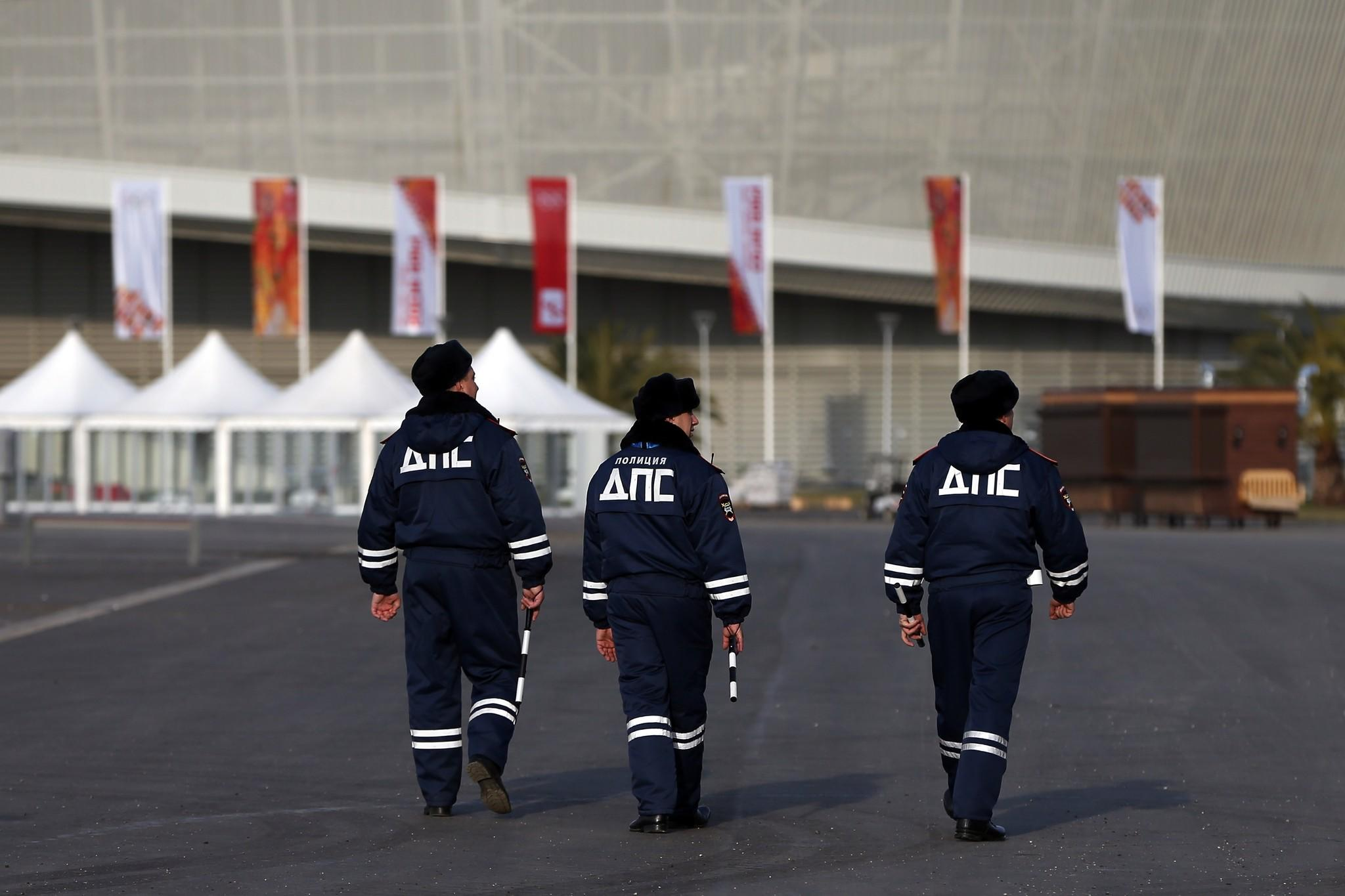Security personnel walk in the Olympic Park in the Coastal Cluster in Alder, Russia.