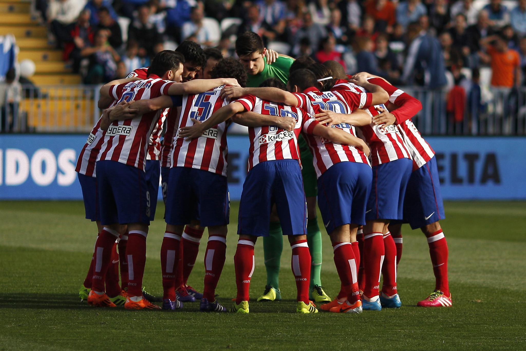 Atletico Madrid players gather before their Spanish First Division soccer match against Malaga at La Rosaleda stadium in Malaga, southern Spain January 4, 2014.