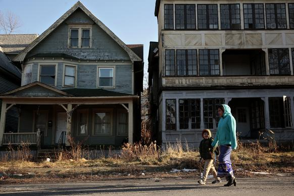 A woman walks her son home from school past dilapidated house