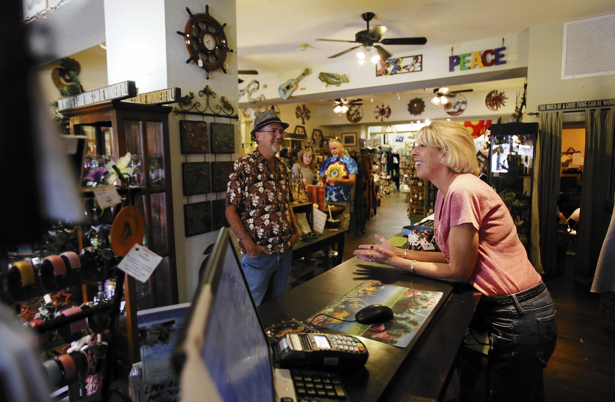 Jim and Kim Pinson, owners of Whispering Winds in downtown Mount Dora, chat at the register on Thursday, December 26, 2013.