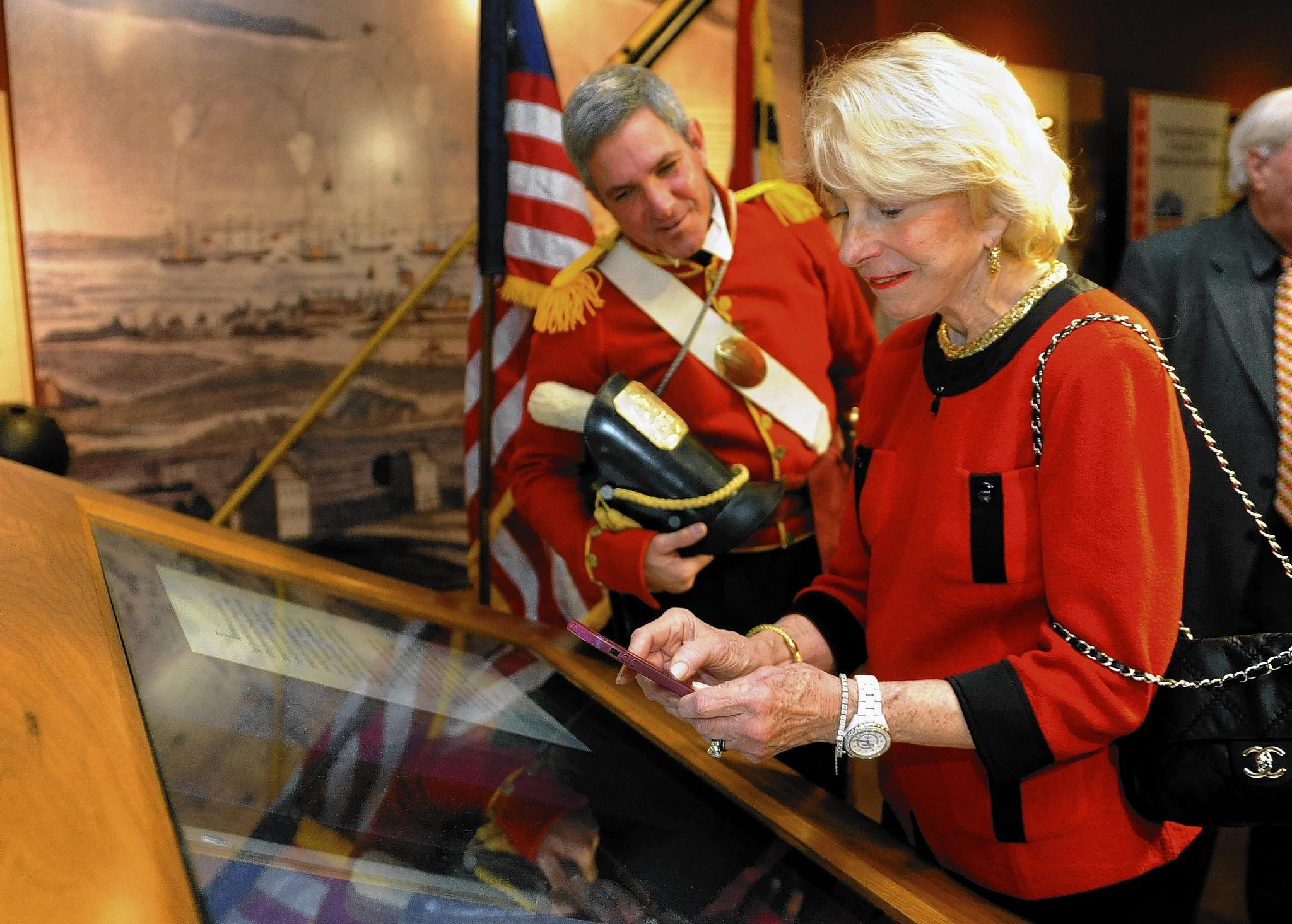 Jayne H. Plank, a Trustee of the Maryland Historical Society, takes a photo of the original Star Spangled Banner which is on display at the Maryland Historical Society.