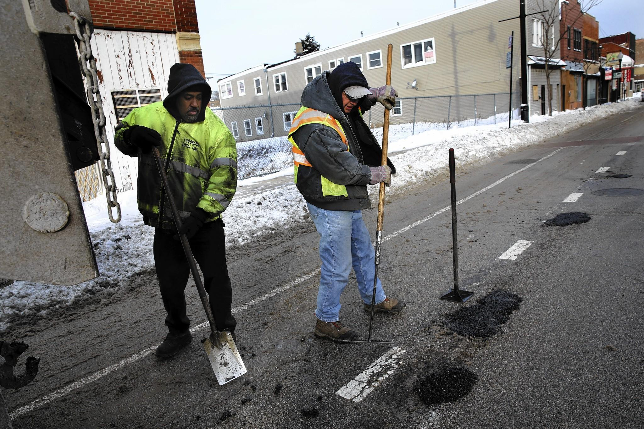 Workers from the city Streets and Sanitation Department fill potholes Wednesday on Halsted Street in Bridgeport.