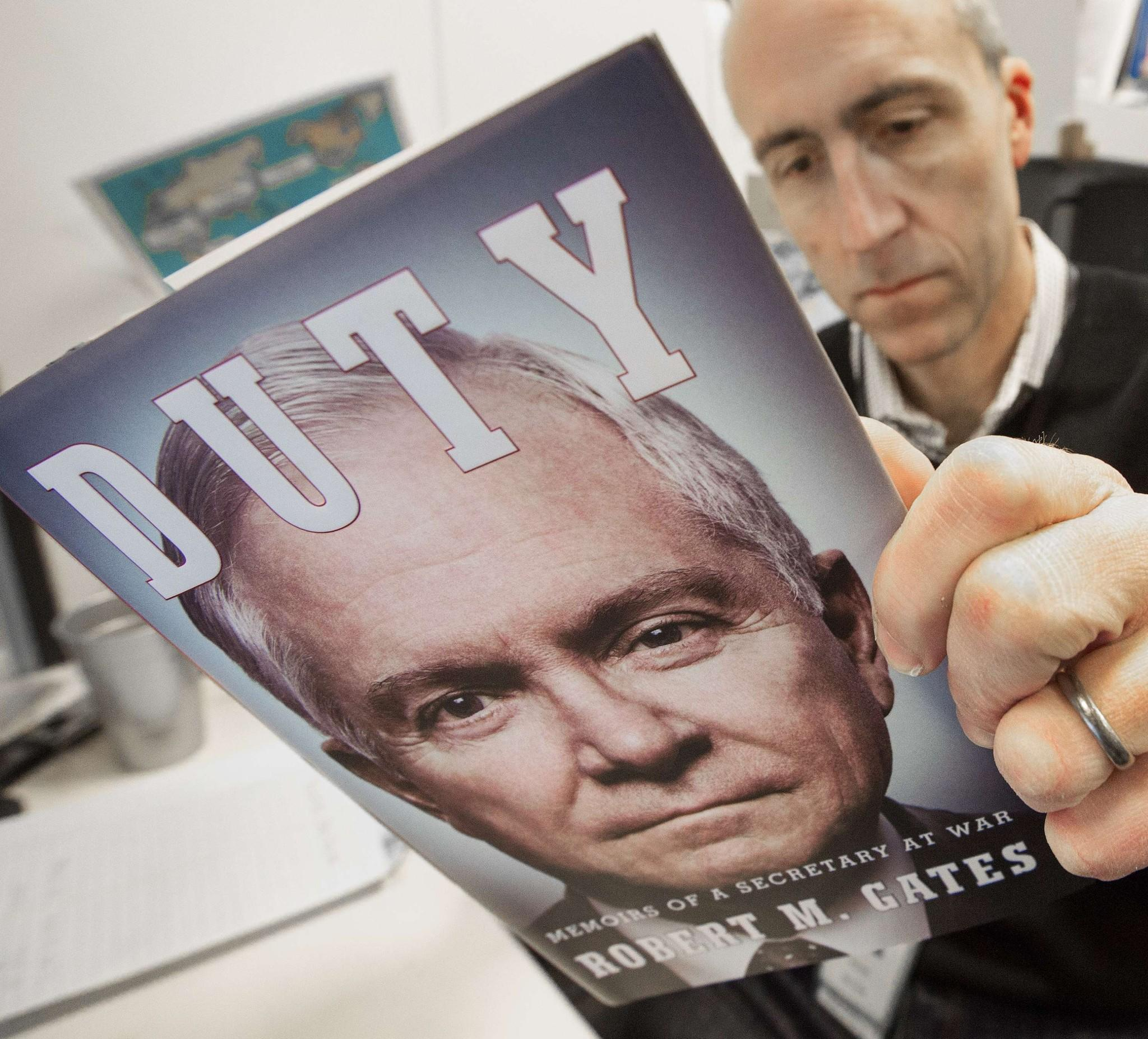 "A journalist reads an advance copy of former U.S. Secretary of Defense Robert M. Gates' book, ""Duty: Memoirs Of A Secretary At War,"" that is circulating among reporters in Washington, D.C."