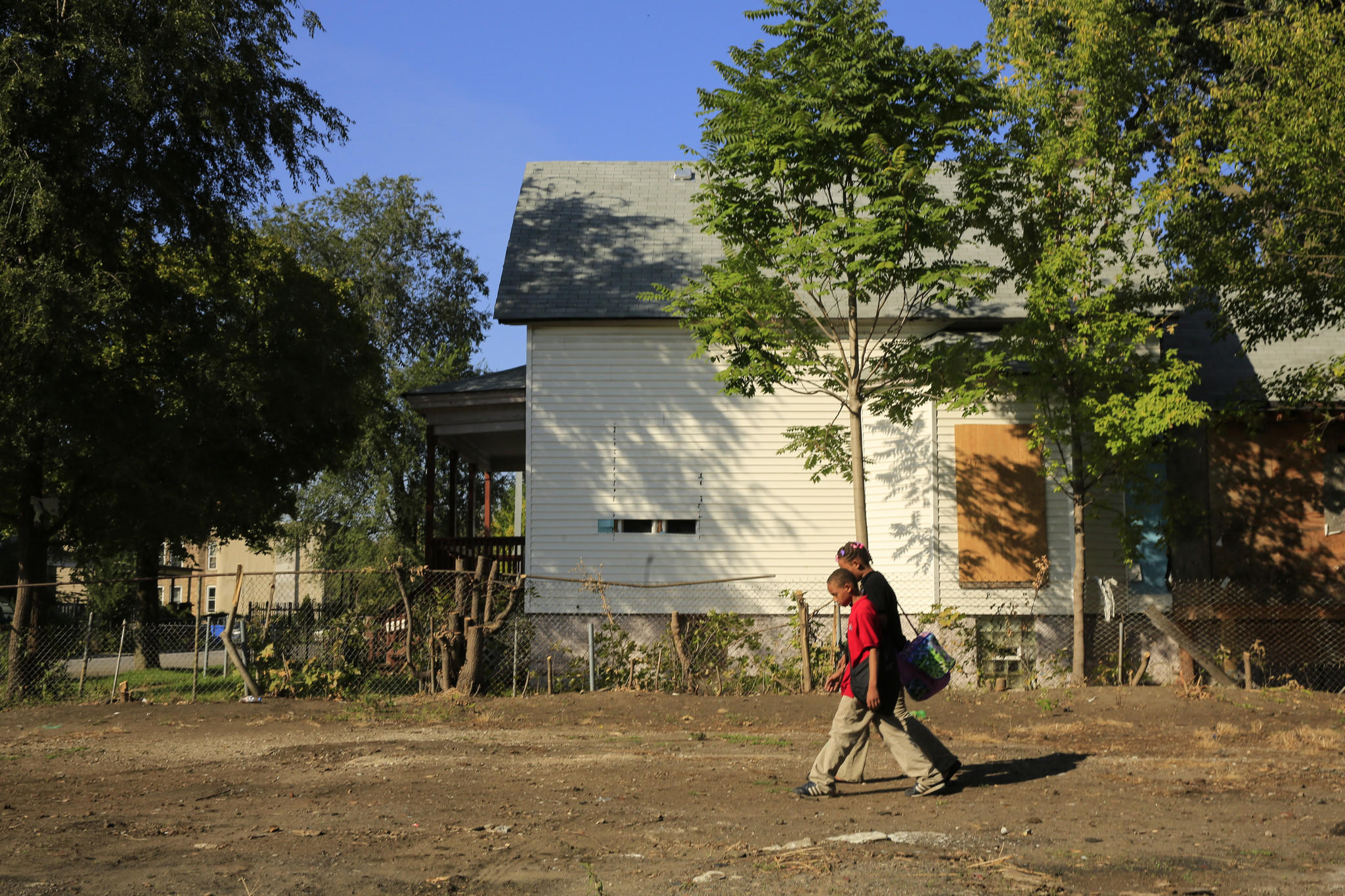 Students from nearby Mays Academy take a shortcut Wednesday, Oct. 2, 2013 across a vacant lot in the Englewood neighborhood on their way home from school.