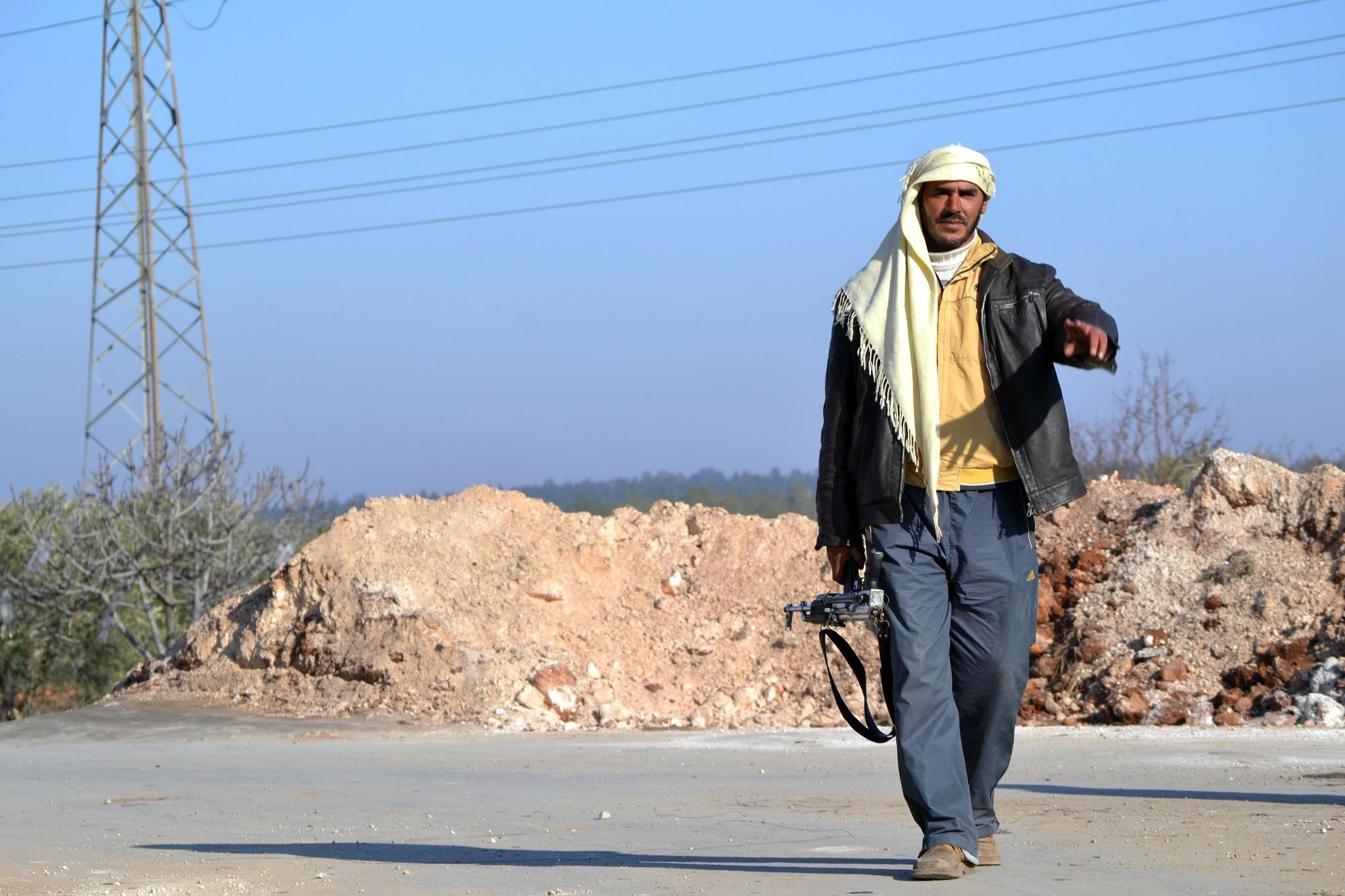 A rebel fighter gestures as he walks towards a checkpoint close to Jabal al-Zawiyaa in Idlib province. The United Nations and the United States hope to launch a peace conference for Syria on Jan. 22.