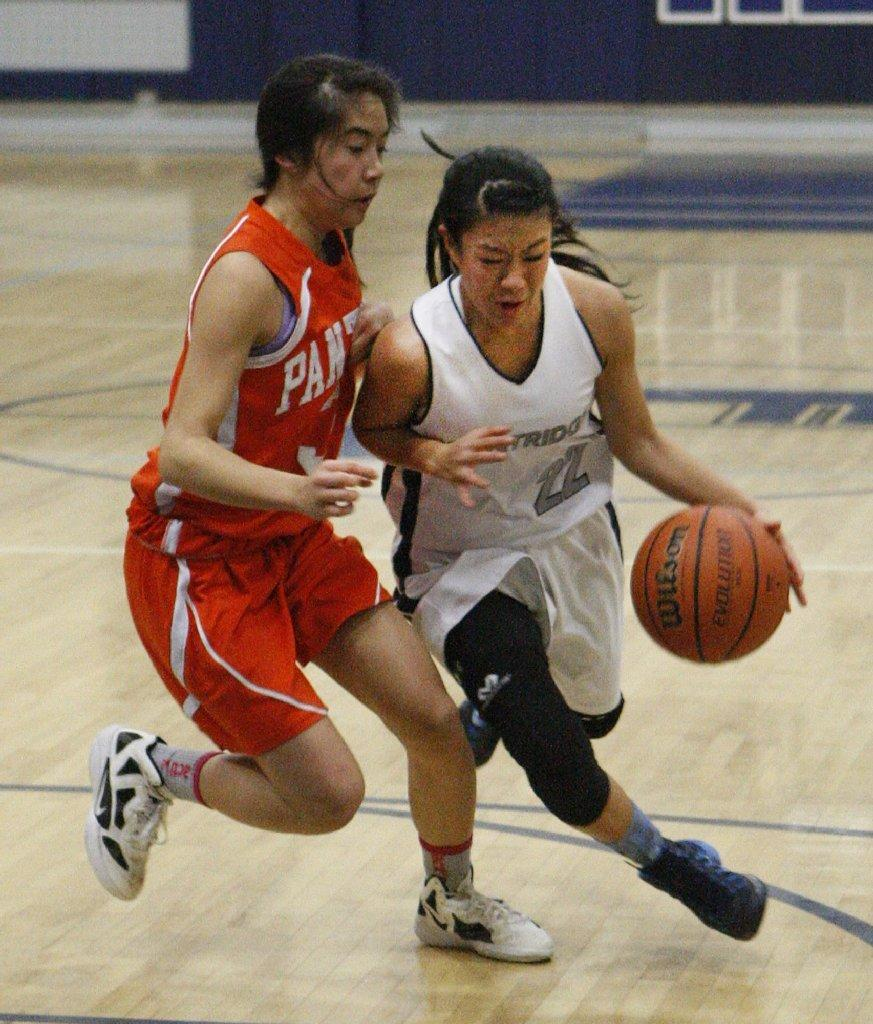 Flintridge Prep's Maya Okamoto is fouled by Pasadena Poly's Kiki Yang and crashed to the floor in a Prep League girls' basketball game at Flintridge Prep on Friday. (Tim Berger/Staff Photographer)